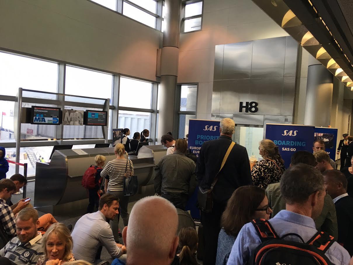 Kø ved gaten da passagererne venter i en time på en forsinket afgang. En forsinkelse, som var skabt af lufthavnen da det indkommende fly måtte vente en time for at komme til en gate.